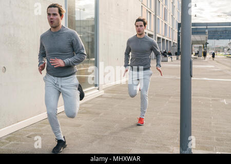 Young adult male twin runners, running along city sidewalk - Stock Photo