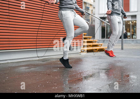 Male adult twins training, skipping with ropes on sidewalk - Stock Photo
