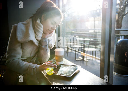 Young girl sitting in coffee shop, using digital tablet, London, England, UK - Stock Photo