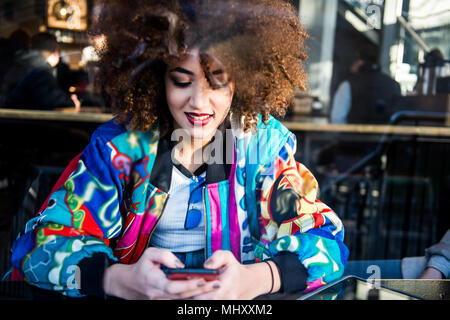 Young girl sitting in bar, using smartphone, view through window, London, England, UK - Stock Photo