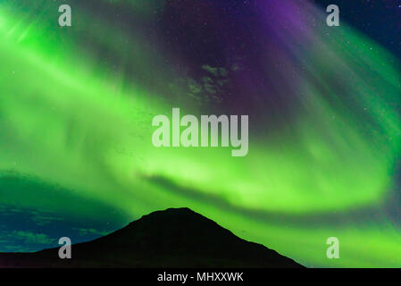 Aurora Borealis above mountain, Narsaq, Vestgronland, Greenland - Stock Photo