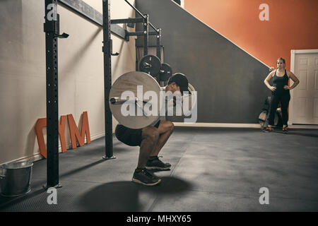 Man in gym weightlifting using barbell - Stock Photo