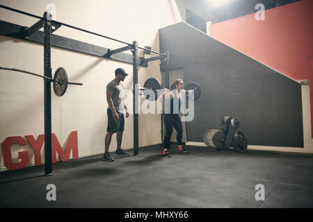 Woman in gym weightlifting using barbell - Stock Photo