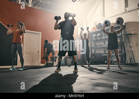 Man using dumbbells in gym - Stock Photo