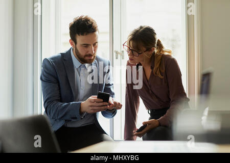 Colleagues in office looking at smartphone - Stock Photo