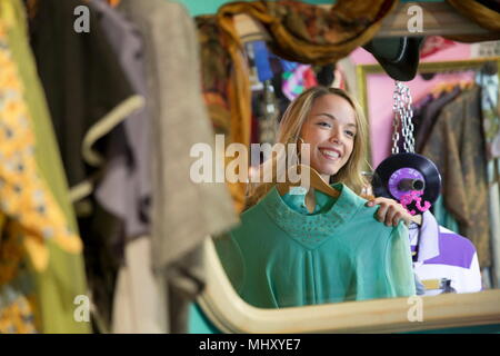 Mirror image of young woman trying on vintage clothes in thrift store - Stock Photo