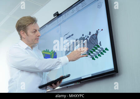 Engineer discussing CAD drawing in engineering factory - Stock Photo