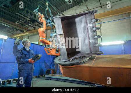 Engineer with controller in robotic welding bay in engineering factory - Stock Photo
