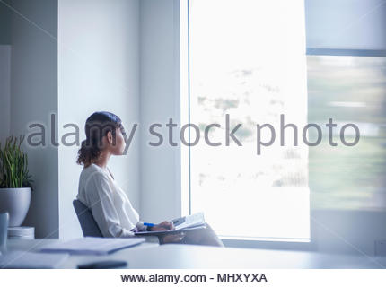 Businesswoman sitting in office looking out of window - Stock Photo