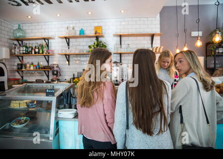 Three female friends, standing at counter in cafe, rear view - Stock Photo
