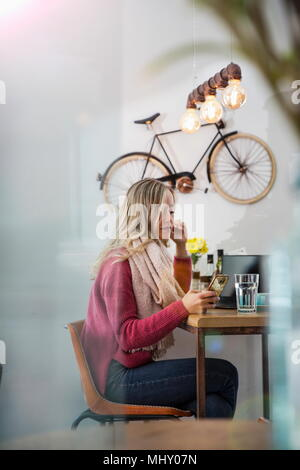 Woman sitting in cafe, looking at smartphone - Stock Photo