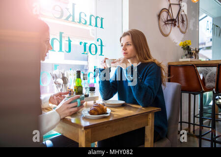 Two female friends sitting together in cafe, drinking coffee - Stock Photo