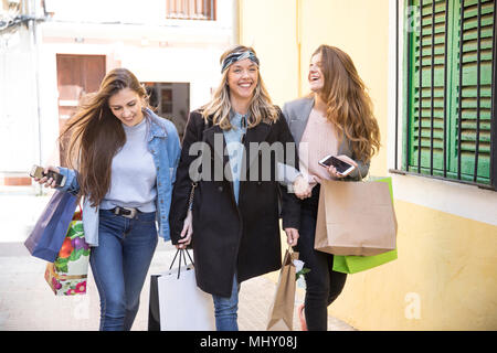Friends out shopping and laughing in street - Stock Photo