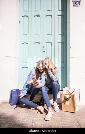 Friends taking selfie on doorstep - Stock Photo