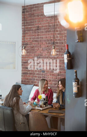Three female friends, sitting together in cafe - Stock Photo