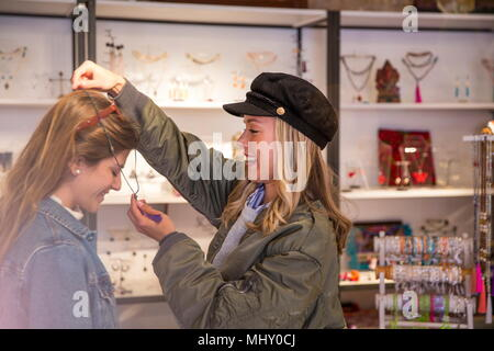 Two female friends, shopping, trying on necklace - Stock Photo