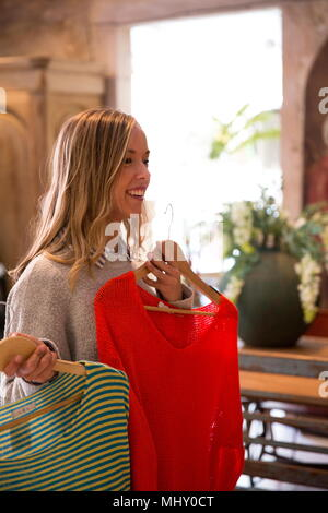 Young woman shopping, holding clothes up, making decisions - Stock Photo