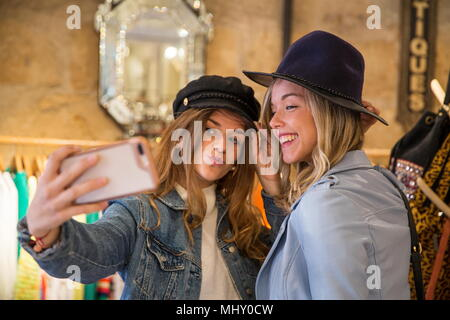 Two friends in shop, trying on hats, taking selfie, using smartphone - Stock Photo