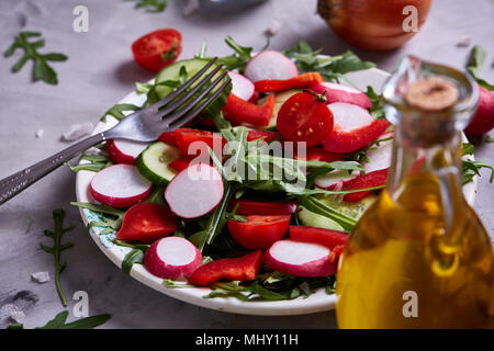 Creative fresh vegetable salad with ruccola, cucumber, tomatoes and raddish on white plate over textured background, close-up, selective focus. Mornin - Stock Photo