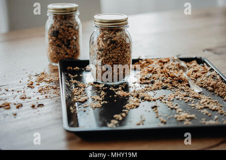 Baking tray with freshly baked homemade granola being filled in two mason jars for storage. - Stock Photo