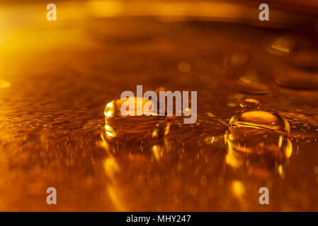 Oil drops and bubbles on a metal gear engine surface. Closeup photo. - Stock Photo