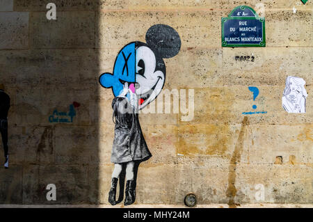 A small girl reaches up to touch Mickey Mouse ,a street painting on a wall on Rue du marché des Blancs Manteaux ,Paris ,France - Stock Photo