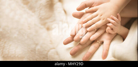 Newborn child hand. Closeup of baby hand into parents hands. Family, maternity and birth concept. Banner - Stock Photo