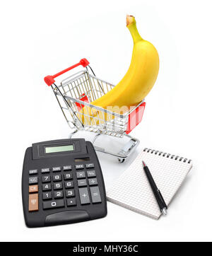 Shopping cart with banana, calculator, notebook paper isolated on white background - Stock Photo