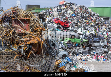 Piles of scrap metal, including cars waiting to be recycled at a processing plant. - Stock Photo