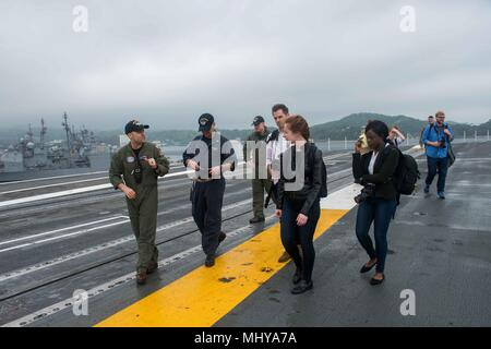 180503-N-CL027-0076 YOKOSUKA, Japan (May 3, 2018) Sailors aboard the Navy's forward-deployed aircraft carrier, USS Ronald Reagan (CVN 76), explains flight deck operations to Northwestern University media students during a ship tour, May 3, 2018. During the tour, the students visited various locations throughout the ship including the flight deck, hangar bay and bridge. Ronald Reagan, the flagship of Carrier Strike Group 5, provides a combat-ready force that protects and defends the collective maritime interests of its allies and partners in the Indo-Pacific region. (U.S. Navy photo by Mass Com - Stock Photo
