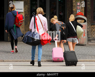 Gothenburg, Sweden - July 1, 2014: Four people with bags on their way to the railway station Centralstationen in Gothenburg. - Stock Photo