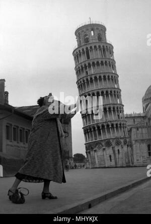 Tessie O'Shea pretends to push the Leaning Tower of Pisa. The Welsh entertainer is on a three-month tour of camps in Germany, Austria and Italy. - Stock Photo
