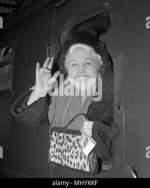 Welsh actress Tessie O'Shea waves from her carriage window as she leaves Waterloo Station, London, on the Pendennis Castle boat train bound for South Africa. - Stock Photo