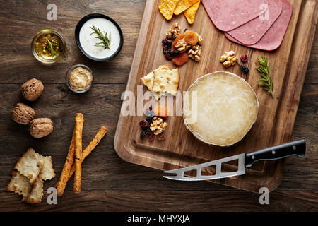 Turkish Karaman skinbag cheese (divle obruk) on a wooden table decorated with props of wooden cutting board, cheese knife and walnuts - Stock Photo
