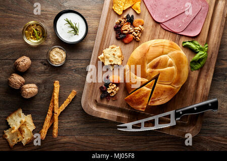 Turkish smoked cheese on a wooden table decorated with props of wooden cutting board, cheese knife, walnuts, dried fruits, ham and olive oil - Stock Photo