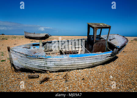 A  wooden fishing boat being restored  on the shingle beach at Dungeness, Sussex, England - Stock Photo