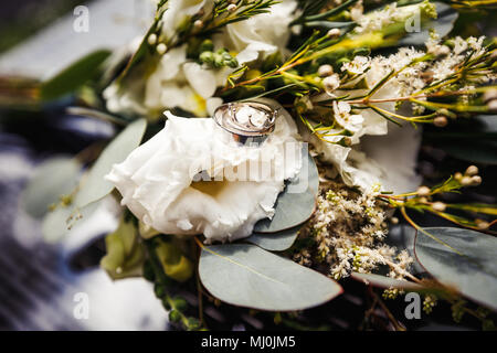 Gold wedding rings on a bouquet of white flowers - Stock Photo