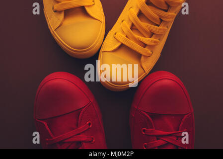 Young people on a love date, conceptual image. Top view of two pair of casual sneakers, yellow and red, from above close to and facing each other like - Stock Photo