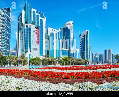 DOHA, QATAR - FEBRUARY 13, 2018: The skyscrapers of Al Dafna district in West Bay neighborhood with beautiful colored flower beds on the foreground, o - Stock Photo