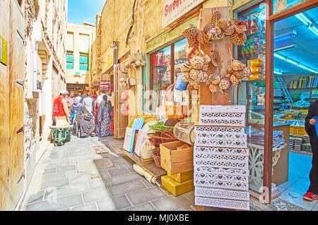 DOHA, QATAR - FEBRUARY 13, 2018: The narrow backstreet of Souq Waqif with row of small shops, on February 13 in Doha - Stock Photo