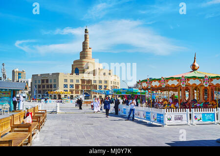 DOHA, QATAR - FEBRUARY 13, 2018: The street of Al Souq district with carousels of Luna park and the scenic building of Al Fanar mosque on the backgrou - Stock Photo