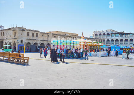 DOHA, QATAR - FEBRUARY 13, 2018: The crowd of children and teens in Amusement Park in old town, next to the buildings of Souq Waqif, on February 13 in - Stock Photo