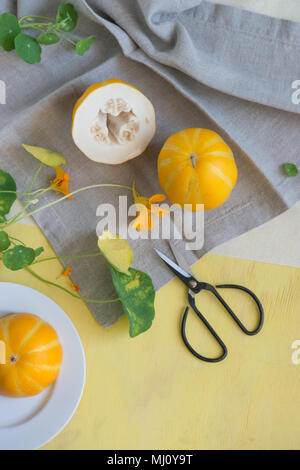 still life with melons and flowers in yellow and gray. - Stock Photo