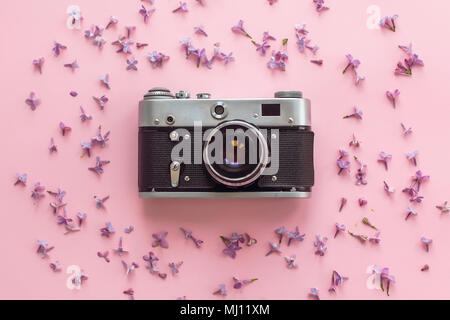 stylish old photo camera on pink background with lilac flowers. creative travel trendy flat lay with space for text. modern fashion and hipster image. - Stock Photo