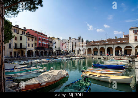 The pretty old harbour in Desenzano del Garda draws locals and tourists to enjoy an early evening aperitivo, Brescia, Lombardy, Italy - Stock Photo