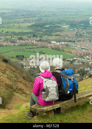 Man and woman couple sitting on a wooden bench on North Hill  above the town of Great Malvern Gloucestershire after walking along the Malvern Hills - Stock Photo