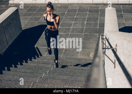 Fit sportswoman running up the steps. Female runner exercising on staircase outdoors. - Stock Photo