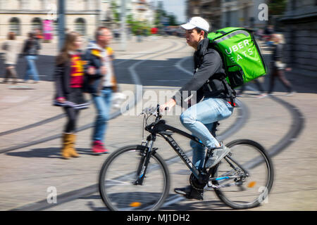 UberEATS / Uber Eats online meal ordering and delivery platform, bicycle courier delivering meals in the city center - Stock Photo