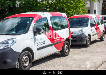 Red-white post delivery cars from Bpost, Belgian company responsible for the delivery of national and international mail - Stock Photo