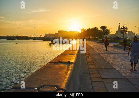 DOHA, QATAR - FEBRUARY 13, 2018: The sunrise over the Corniche promenade with a view on traditional dhow boats in harbor and row of palms along the wa